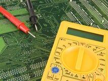 Yellow multimeter. On green pcb Stock Photo