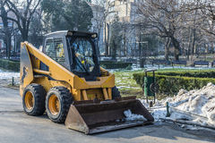 Yellow municipality excavator doing spring cleaning in central park. Of the city Royalty Free Stock Photo