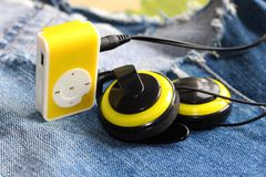 Yellow music player and beautiful overhead headphones. Lux Stock Image