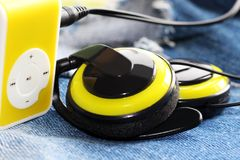 Yellow music player and beautiful overhead headphones. Lux Stock Photos