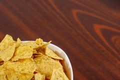 Yellow nacho in white bowl on the wooden table.  stock images