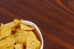 Yellow nacho in white bowl on the wooden table.  royalty free stock photos