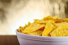 Yellow nacho in white bowl on the wooden table.  stock photo