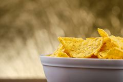 Yellow nacho in white bowl on the wooden table.  royalty free stock photography