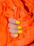Yellow nails manicure. Orange background royalty free stock photography
