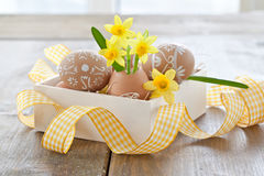 Yellow narcissus in egg shell. And painted easter eggs Royalty Free Stock Image