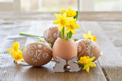 Yellow narcissus in egg shell. On rustic wood Royalty Free Stock Photography