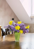 Yellow narcissus  flowers and lilac  in a green glass vase on a wooden table Stock Photography