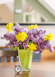 Yellow narcissus  flowers and lilac  in a green glass vase on a wooden table Royalty Free Stock Photo
