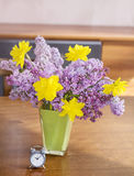Yellow narcissus  flowers and lilac  in a green glass vase on a wooden table Royalty Free Stock Images
