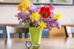 Yellow narcissus  flowers and lilac  in a green glass vase on a wooden table Stock Image