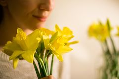 A smiling girl with a bouquet of yellow spring flowers, narcissus Royalty Free Stock Images