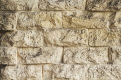 Yellow natural stone brick wall photo texture. Rough pale stone bricks surface design. Stock Photography