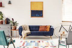 Yellow and navy blue painting above sofa in modern living room i. Nterior with bike. Real photo stock photography