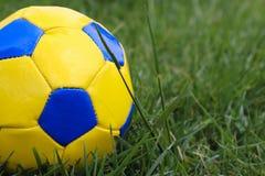 Yellow navy blue soccer ball on grass stock photos