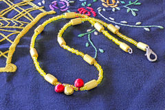 Yellow necklace on a napkin hand-emboikered doily. Yellow necklace on a colorful napkin  hand-emboikered doily Royalty Free Stock Photos