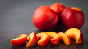 Yellow nectarine peach and slices on grungy background Stock Photos