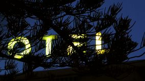 Yellow neon hotel sign as seen from through a pine tree stock video footage