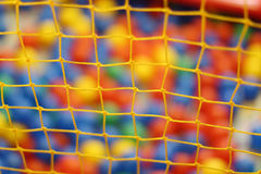 Yellow net and many colored toy balls in children playground Royalty Free Stock Images