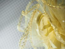 Yellow netted fabric, wrapped with ribbon. On gray tartan background Stock Photography