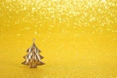 Yellow New Year background with decorative Christmas tree. Decorative metal Christmas tree on a yellow shiny background Stock Image