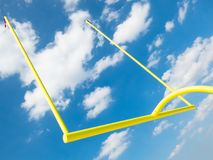 NFL Football Goalpost, Goal Post. A yellow NFL American football goalpost. The goal post stands upright with a blue sky and clouds as a background Royalty Free Stock Photo