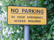 A yellow no parking 24 hour emergency access required post metal Stock Photo