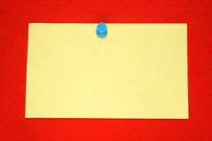 A yellow note. Held on a red felt notice board with a blue push-pin Royalty Free Stock Images