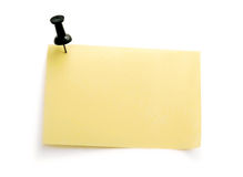 Yellow note with black pin Stock Image