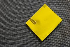 Yellow note and clip into blue corkboard royalty free stock photo