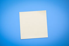 Yellow note over blue background. One clean yellow note over blue background Stock Photos