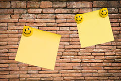 Yellow note pad on brick wall Royalty Free Stock Images