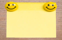 Yellow note pad on brick wall Royalty Free Stock Photo
