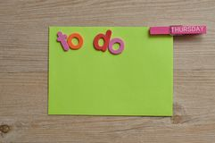 A yellow note pad with the word to do and a peg attached with the word thursday on it. On a wooden background stock photography