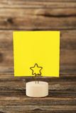 Yellow note paper on a holder on brown wooden background. Royalty Free Stock Images