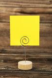 Yellow note paper on a holder on brown wooden background. Royalty Free Stock Photos