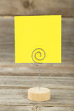 Yellow note paper on a holder on grey wooden background. Stock Image