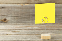 Yellow note paper on a holder on grey wooden background. Stock Photos