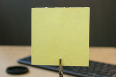 Yellow note paper on a holder. Note paper on a holder. Place for text. Reminder paper sheet for notes. Blank sticker for notes on the table Stock Photos