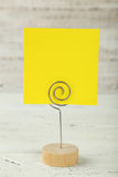 Yellow note paper on a holder on white wooden background. Stock Photos