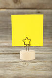 Yellow note paper on a holder on wooden background Stock Photography