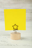 Yellow note paper on a holder on wooden background Royalty Free Stock Images