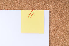 Yellow Note Paper with Paperclip on White Paper  Stock Photos
