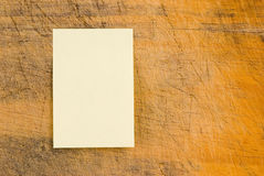 Yellow note paper on retro wood Stock Images