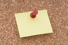 Yellow Note Paper With Tack on Cork Surface Stock Photo