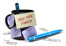 Losing Job Concept, Unemployment, You Are Fired. Yellow note where it's handwritten you are fired glued on a black mug with other notes. On the floor there is Royalty Free Stock Photo