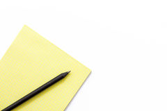 Yellow notebook and black pencil on a white background. Minimal business concept. Flat lay. Top view Stock Photos