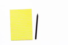 Yellow notebook and black pencil on a white background. Minimal business concept for office. Flat lay. Top view Stock Photography