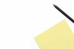 Yellow notebook and black pencil on a white background. Minimal business concept. Stock Photo