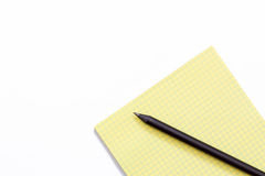 Yellow Notepad and black pencil on white background. Royalty Free Stock Photography